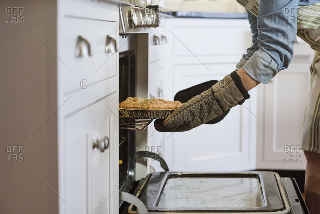 Person pulling fresh baked pie out of the oven