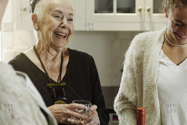 Women in a kitchen laughing while drinking wine