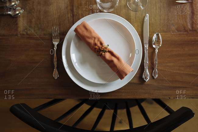 Place setting at a table with orange napkin