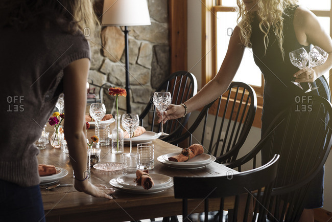 Women setting table for Thanksgiving dinner party