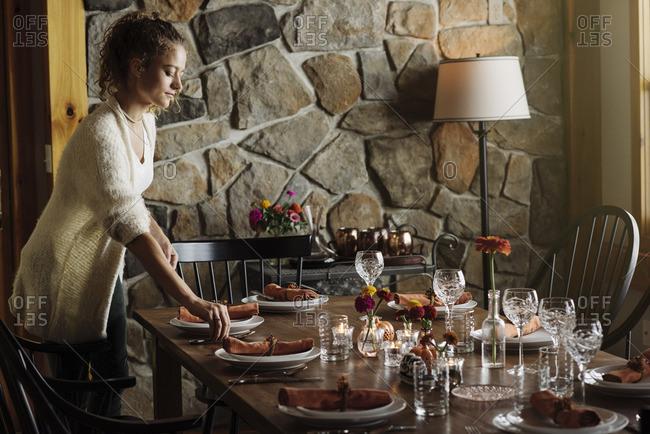 Teen girl setting table for Thanksgiving dinner party
