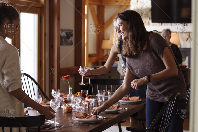 Women setting table for Thanksgiving dinner party together