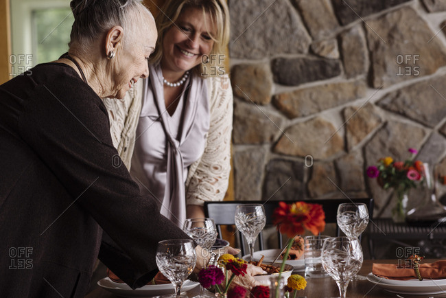 Women setting foot at the table for Thanksgiving dinner party