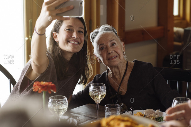 Woman taking selfie with her grandmother at Thanksgiving dinner