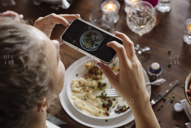 Teen girl taking picture of her plate at Thanksgiving dinner