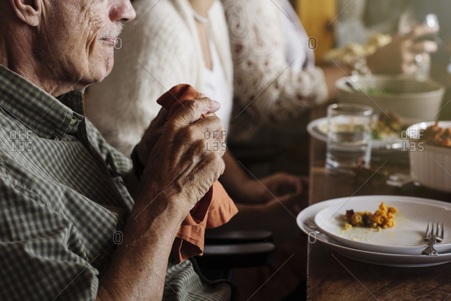 Senior man holding orange napkin at Thanksgiving dinner
