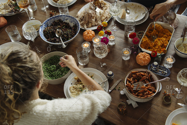Family dishing out food at Thanksgiving dinner