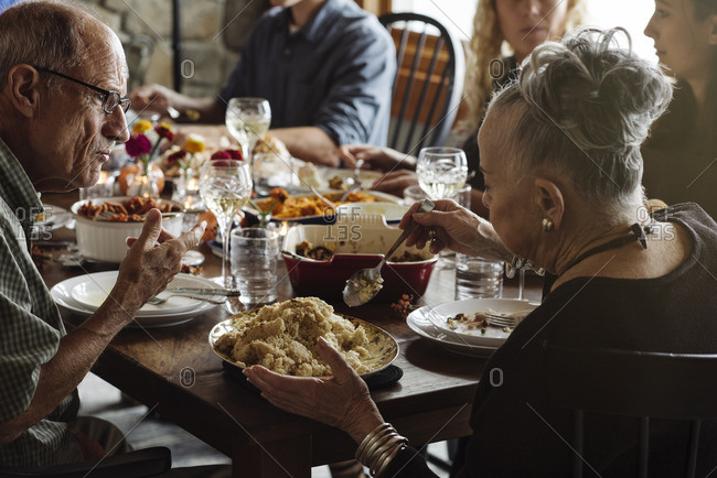 Senior woman serving stuffing at Thanksgiving dinner