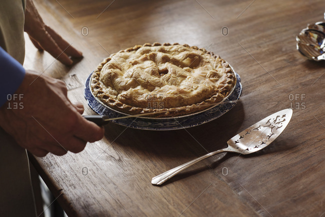 Person slicing fresh baked pie for Thanksgiving dessert