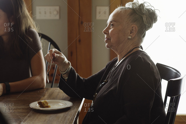 Senior woman eating a slice of pie at a Thanksgiving gathering