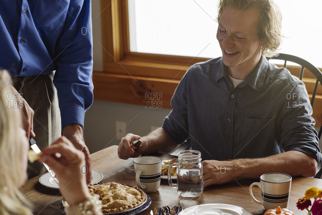Man passing out fresh baked pie for Thanksgiving dessert