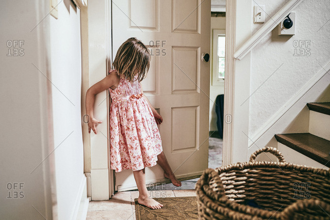 Little girl holding door open with her foot