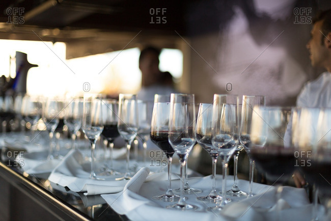 Wine glasses on trays on bar with servers in background
