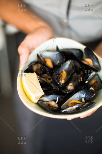 Person holding dish of mussels with lemon