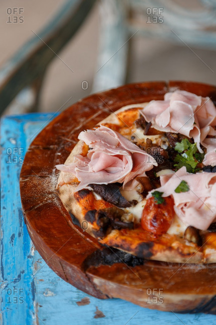 Rustic pizza with ham on wooden slab