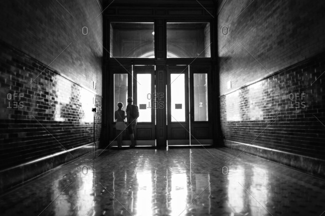 Couple standing at the doors at end of long tiled hallway