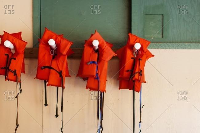 Orange life vests hanging on wooden pegs