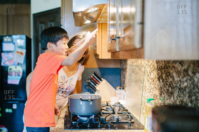 Boy tasting food while mom teaches him how to cook