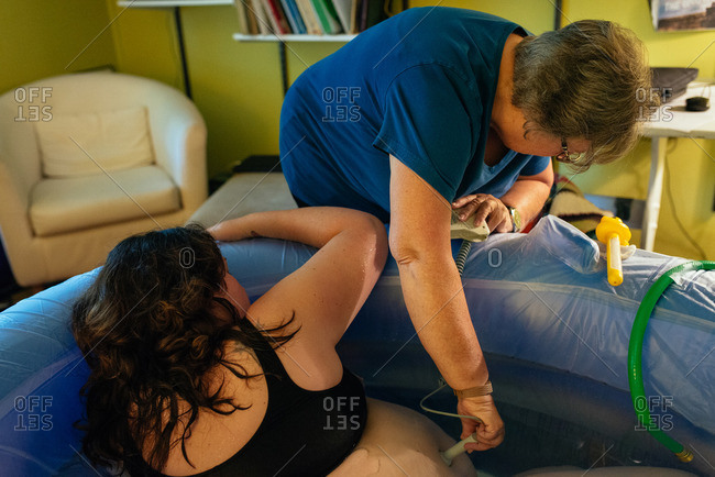 Midwife checking a pregnant woman during home delivery