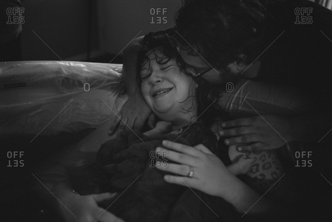 Woman in a birthing tub holding her baby with her husband at her side