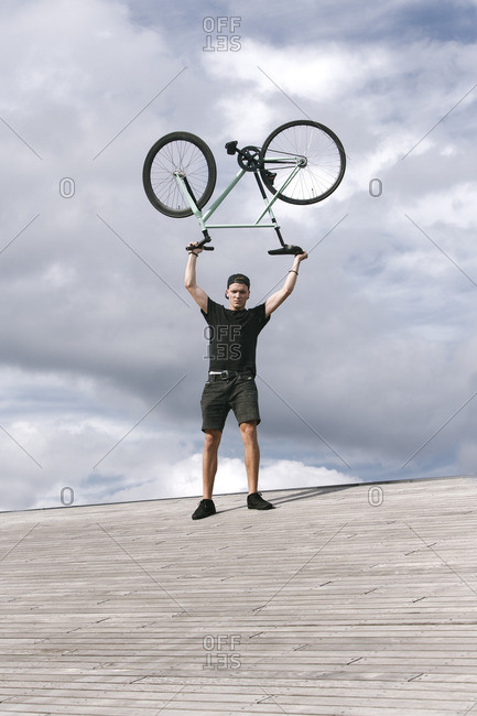 Portrait of strong young man holding bike up in the sky