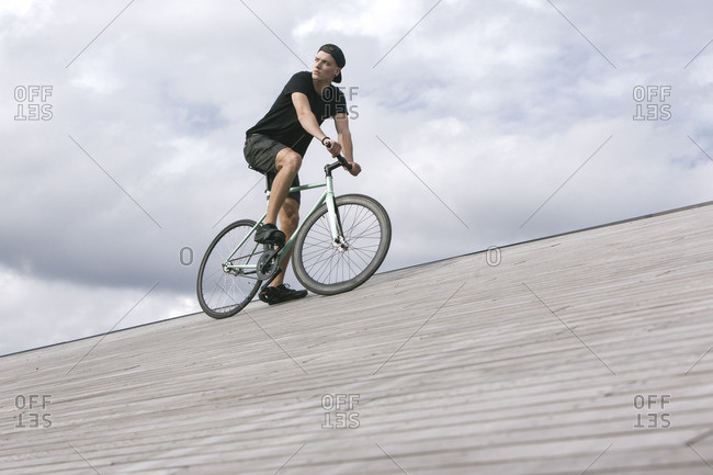 Young man riding bicycle on wooden surface against of cloudy sky