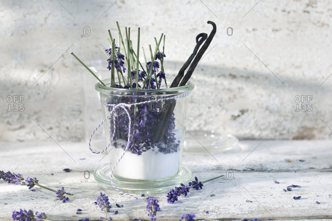Glass of lavender sugar with lavender blossoms and vanilla beans