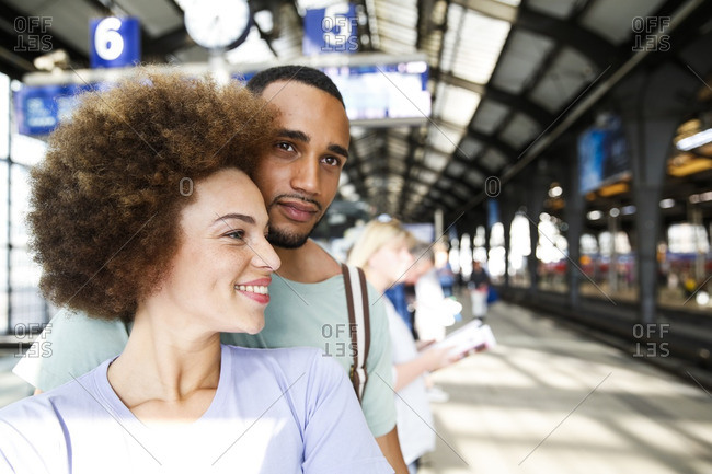 Happy young couple waiting for commuter train
