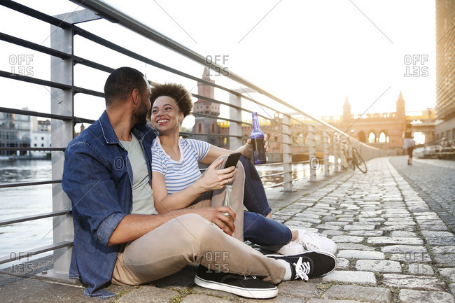 Couple sitting by river holding bottles and smart phone