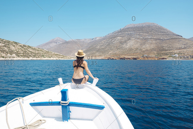 Greece- back view of woman sitting on bow of a boat looking at Amorgos Island