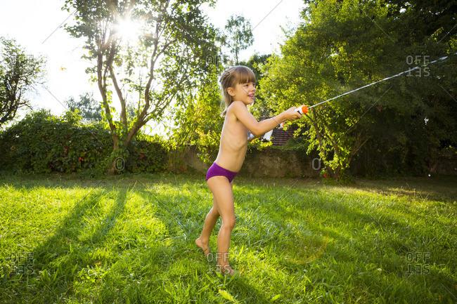 Little girl splashing water with water gun