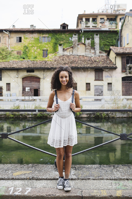 Italy- Milan- portrait of smiling young woman with backpack wearing white summer dress
