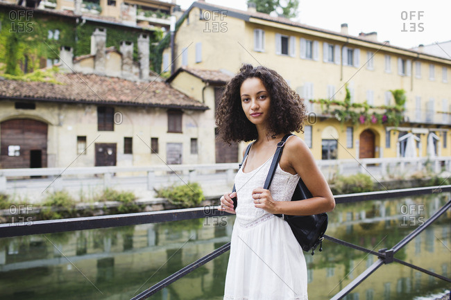 Italy- Milan- portrait of young woman with backpack wearing white summer dress