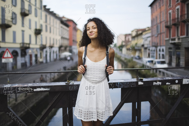 Italy- Milan- portrait of smiling young woman with backpack wearing white summer dress standing on a bridge