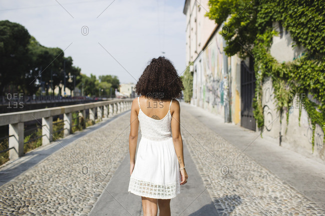 Back view of walking young woman wearing white summer dress