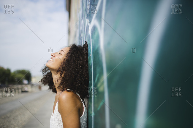 Smiling young woman with eyes closed leaning against wall