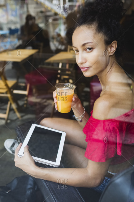 Young woman with glass of orange juice and tablet looking through window of a coffee shop