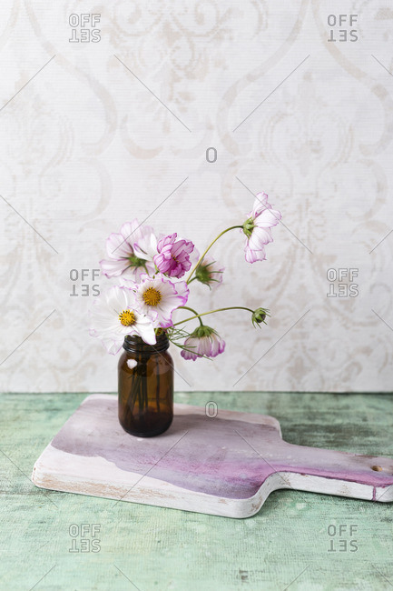 Flowers in a vase on a pink chopping board