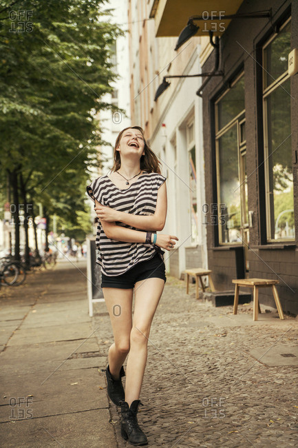 Germany- Berlin- laughing young woman walking on pavement