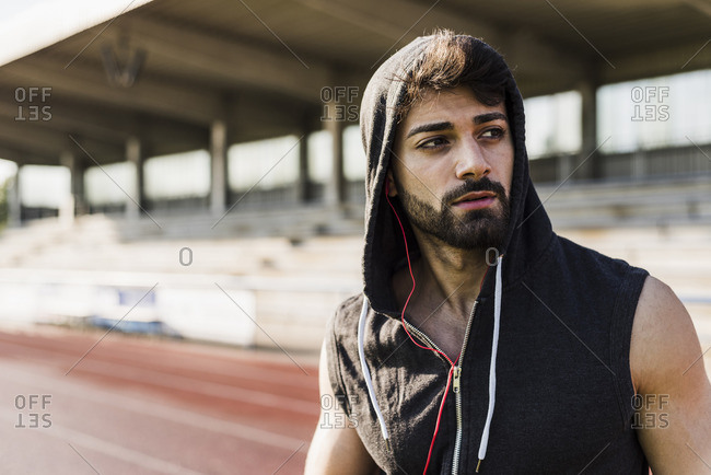 Young man wearing hooded top on tartan track
