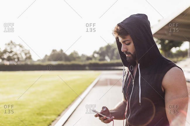 Young man with cell phone wearing hooded top on tartan track