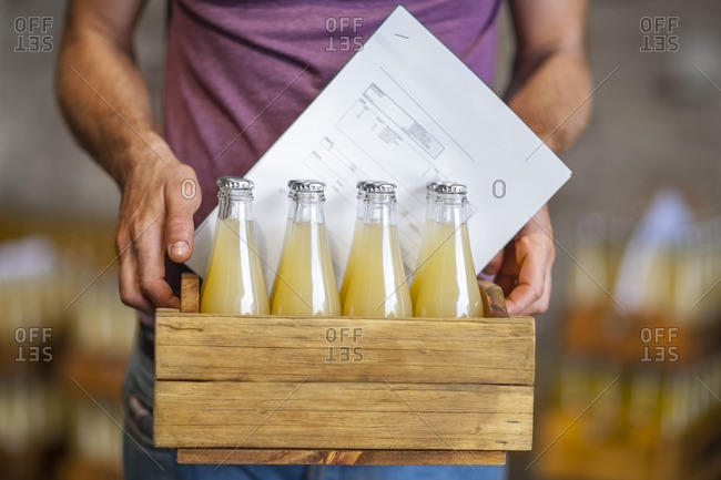 Man carrying wooden box with bottles of juice in warehouse