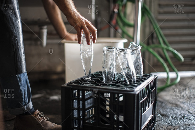 Man placing clean empty glass bottles on crate