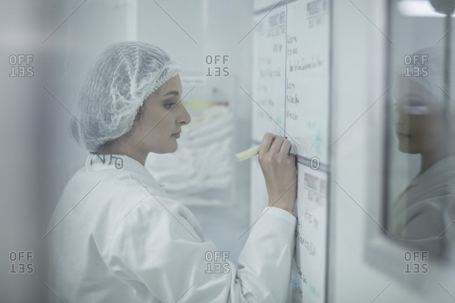 Lab technician in sterile protective clothing writing notes on whiteboard