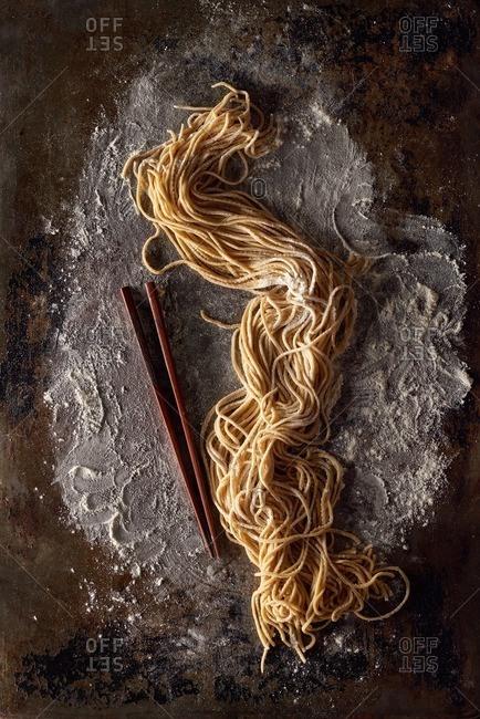 Handmade ramen on a floured surface next to chop sticks