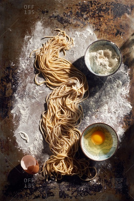 Homemade ramen on a floured surface next to a bowl of eggs and flour
