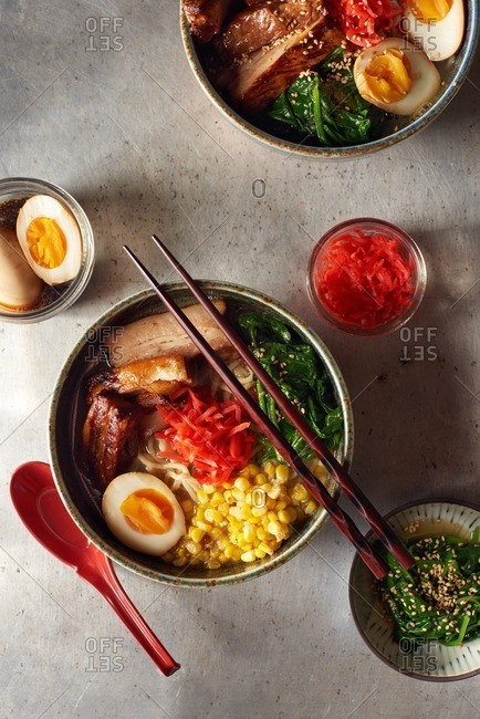 Pork belly ramen in an artisanal Japanese bowl served with a soft boiled egg, cooked spinach, sauteed corn and pickled red ginger
