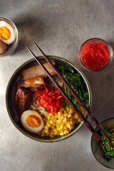 Pork belly ramen in a bowl served with a soft boiled egg, cooked spinach, sauteed corn and pickled red ginger