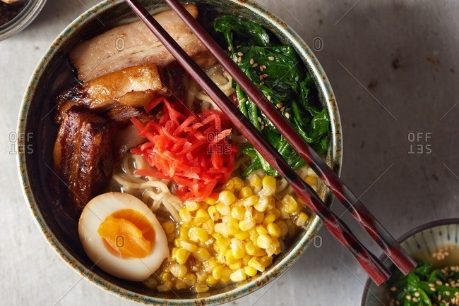 Pork belly ramen served with a soft boiled egg, cooked spinach, sauteed corn, pickled red ginger and chopsticks