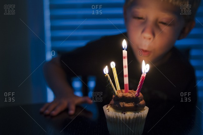 Boy blowing out candles on his birthday cupcake
